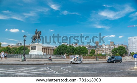 The equestrian statue of Henry IV by Pont Neuf, Paris, France. Traffic on the road, blue cloudy sky at summer day