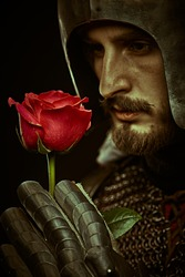 The era of romanticism. Close-up portrait of a noble knight in armor with a red rose in his hands.