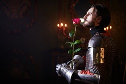 The era of romanticism. Portrait of a noble knight in armor with a red rose in his hands standing in a castle.
