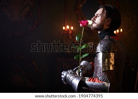The era of romanticism. Portrait of a noble knight in armor with a red rose in his hands standing in a castle. Stok fotoğraf ©