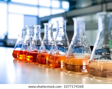The Erlenmeyer or Conical flask on bench laboratory, with gradient solvent for analysis concentration range of iron show the orange color, detect with UV-spectrophotometer. Selective focus.