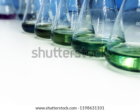The Erlenmeyer or Conical flask on bench laboratory, with green solvent from forming reaction between boric acid and ammonia solution analysis concentration in wastewater sample. Selective focus.