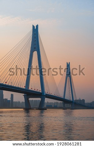 "The Erqi Yangtze River Bridge in the sunset,the text on the bridge is the name ""Erqi Yangtze River Bridge"""