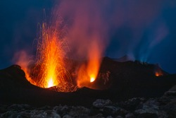 The eruption of active volcano Stromboli spraying lava into the night, shot in blue hour in Italy.