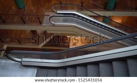 The escalators. A modern interior of the supermarket with escalator stairs. The shopping center with nobody people.