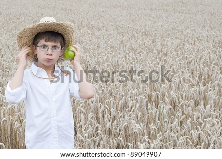 The European school-age boy in a straw hat with a green apple in his hand against the background of a wheat field