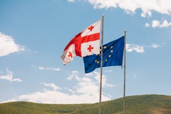The European Union and Georgian flags fly beside each other, on a background mountain and sky