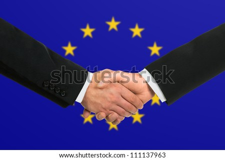 The European Union Flag and business handshake - stock photo
