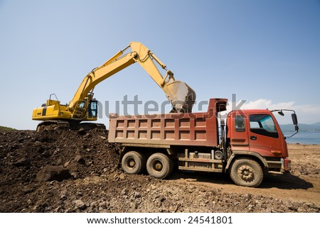 The excavator loads a truck an earthen ground - stock photo