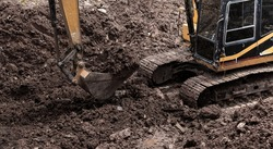 The excavator performs excavation work on the construction site. Crawler excavator digs in shale layer, excavator. Earth-moving equipment, Excavator work
