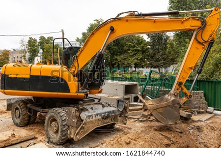 The excavator performs work at a construction site. The construction site is fenced.