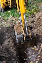 The excavator shovels earth with clay from the pit with a bucket for the construction of a septic tank. Ground work of the machine.
