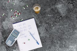 the excessive consumption of alcohol, drugs and medicines damages health and hinders learning, hand-written notes. calculator beer glass and pills on a grey marble table