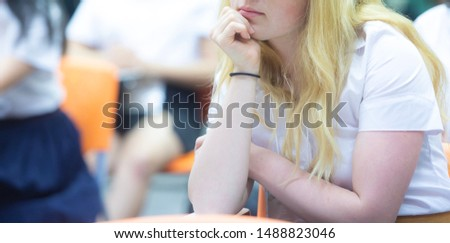 The exchange student with blond hair is sitting on the lecture chair and lean one's chin on one's hand during the lecture with blurred background, academic, focussing, concentrate concept. #1488823046