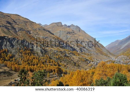 the exclusive alpine resort of Zermatt surrounded by forests in the colors of fall and mountains