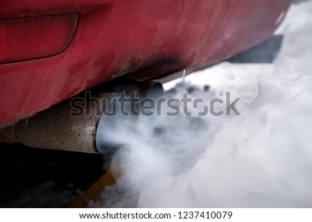 the exhaust gases of the car white thick smoke from the chimney in the winter against the white snow, pollution ecology