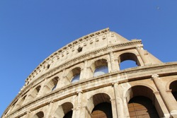 The exterior facade of the Colosseum or Coliseum with the arches against blue clear sky in Rome, Italy