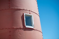 The exterior of a tall red vintage metal round lighthouse with a small glass window. The trim is white around the closed window. The layers are joined with rivets. The background is sky blue.
