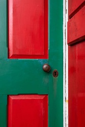 The exterior of a vintage red wooden shingled wall of a building with a bright red and vibrant green criss cross door. There are a rusty doorknob and keyhole in the door. The view is of the corner.