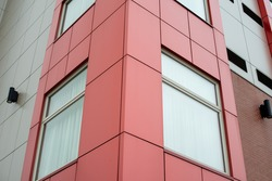 The exterior surface of an aluminum metal composite panel wall of a contemporary business skyscraper. The material is a steel engineered tiled wall siding giving a futuristic and modern look.