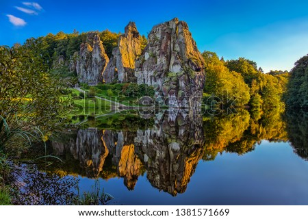 The Externsteine in the evening at sunset with the lake in the foreground and beautiful reflections in the water. #1381571669