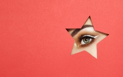 The Eyes of the Young Beautiful Woman with Bright Golden Shadows and Expressive Eyebrows, Looks in the Star Shaped Pattern out of Colored Paper. Star. Christmas Patterns. Red Paper