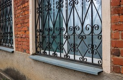 The fa ade on the side. Windows with iron bars with the ligature