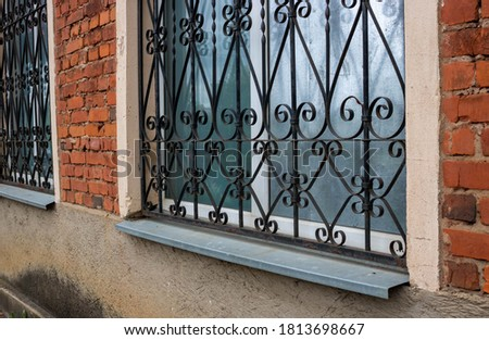 The fa ade on the side. Windows with iron bars with the ligature Photo stock ©