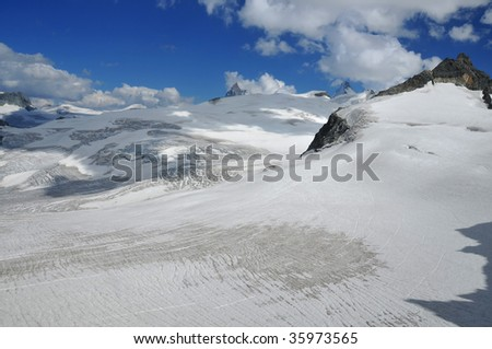 The fabled peak of the matterhorn rises above a sea of ice. to the right another high peak, the Dent d'Herens can also be seen