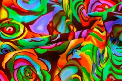 The fabric is bright and colorful, with a pattern of roses all over the fabric, stylized as watercolor paints.