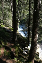 The fabulous alpine waterfalls of Riva in the Dolomites (Campo Tures). Path of San Francesco with Tobl Castle ruins. Lovely place in the Alps. Sunny spring day with no people. Trentino Alto Adige.
