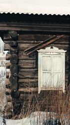 the facade of a dilapidated wooden house in a remote village in western Siberia