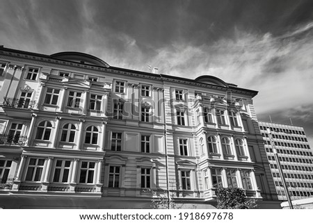 the facade of a historic tenement house and a modern office building in Poznan, monochrome Photo stock ©