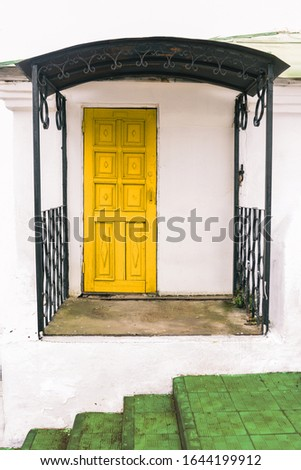 The facade of a small house with white walls, a yellow door and a green staircase. City space, architecture.