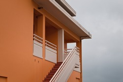 The facade of a yellow house with white balconies and a concrete staircase (Pesaro, Italy, Europe)