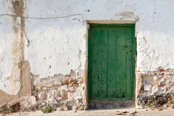 The facade of an old and rustic house, with a green door