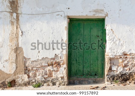 The facade of an old and rustic house, with a green door - stock photo