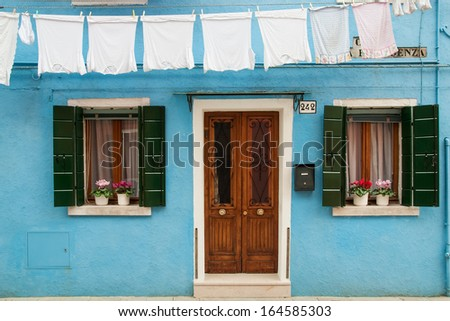 The facade of blue house with windows, door and washing on the island of Burano (Venice, Veneto, Italy).