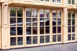 the facade of the restaurant with panoramic beige wooden windows and square glass italian style cafe architecture side view, nobody.