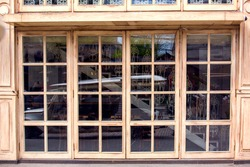 the facade of the restaurant with panoramic beige wooden windows and square glass Spanish style cafe architecture, nobody.