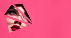 the face of a young beautiful girl with a bright make-up and with plump red lips peeks into a hole in pink paper.Fashion, beauty, make-up, cosmetics, beauty salon, style, personal care, geometry.