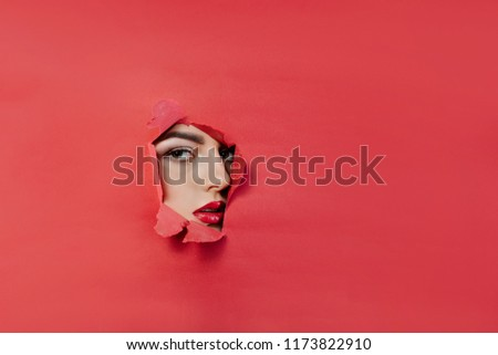 the face of a young beautiful girl with a bright make-up and with plump red lips peeks into a hole in pink paper.Lipstick,cosmetics,makeup, fashion, beauty,beauty salon. #1173822910