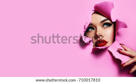 the face of a young beautiful girl with a bright make-up and with plump red lips peeks into a hole in pink paper. Nails with bright red lacquer.Lipstick,cosmetics,makeup, fashion, beauty,beauty salon. #710017810