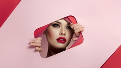 The face of a young beautiful girl with bright makeup and with puffy pink lips looks into the cutout of pink paper.