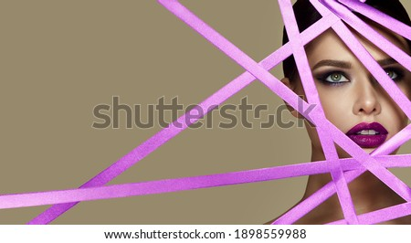 The face of a young woman with bright makeup looks through the stripes of lilac color. Lilac shiny ribbons. Photo stock ©