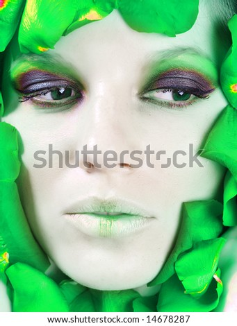 The face of beautiful young girl is surrounded by petals of green rose