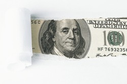 The face of Benjamin Franklin on a hundred-dollar bill, from a torn window in white paper. Background, white. Isolated. Close-up. A hundred-dollar American bill with the eyes of Benjamin Franklin