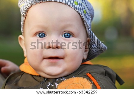 The face of the one-year-old child on a green background, a close up