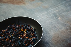The failure on kitchen: burnt charred vegetables. Frying pan with refried black onion and overcooked orange carrots. Cooking fail concept background with copy space.