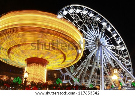 The fair in motion six and big wheel, George Square, Glasgow, Scotland, part of the Christmas and Hogmanay holiday attractions, at night